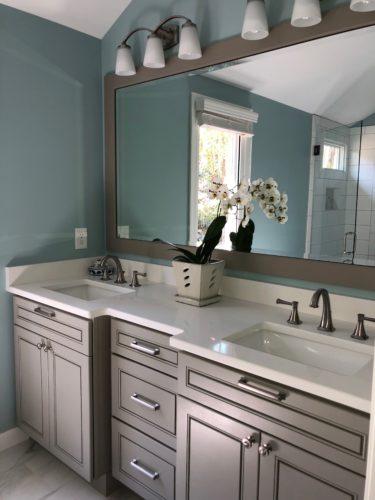 Warm gray vanity and white countertops