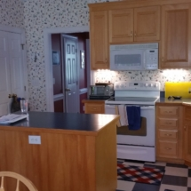 Before - honey wood, checkerboard sheet vinyl, and wallpaper galore