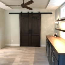 Going nuts with walnut: custom barn doors, floating shelves, and counter atop blue bar cabinets
