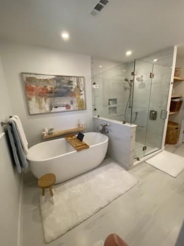 freestanding tub beside white shower